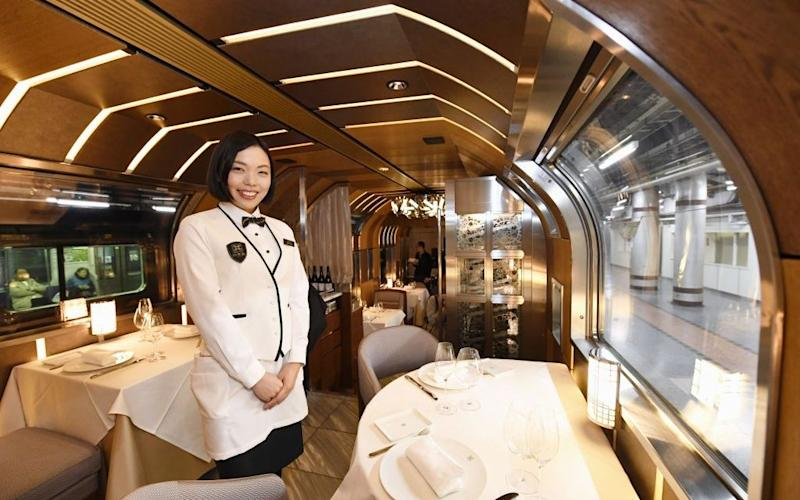 A waitress in the dining room of the newly unveiled Train Suite Shiki-Shima - Credit: Getty