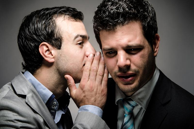 One businessman whispering to another.