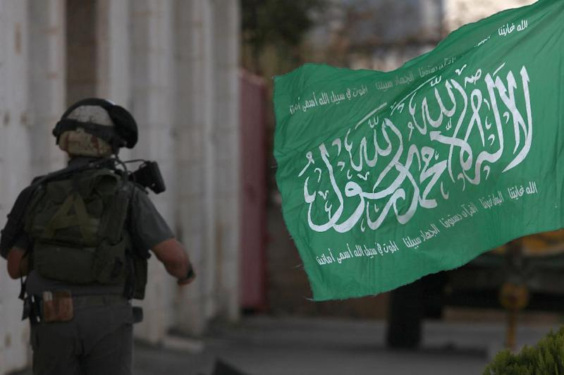 An Israeli soldier runs past a flag belonging to the ruling Hamas movement in the Gaza Strip, on November 17, 2012