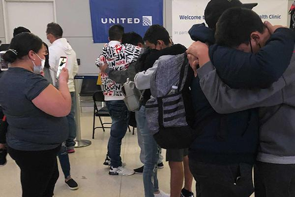 In the background, Elmer hugs his sister as his mother records in Newark Liberty International Airport on Sunday, May 2, 2021. / Credit: CBS News