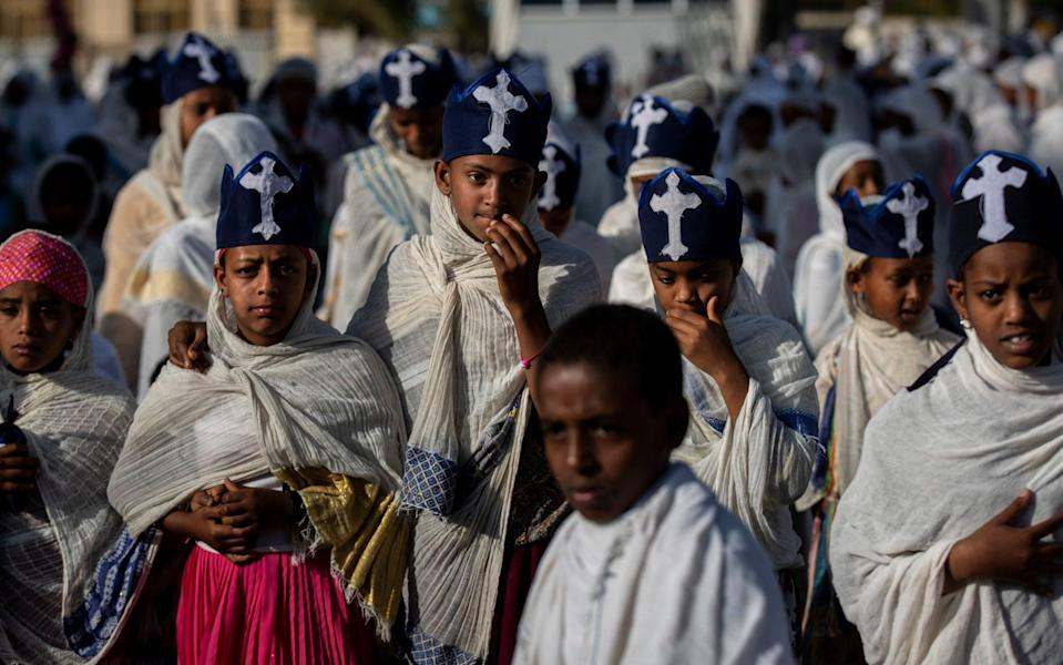 Young members of the choir walk amongst congregants during a Sunday morning service of the Ethiopian Orthodox Tewahedo Church at the Church of St. Mary in Mekele, in the Tigray region of northern Ethiopia - Ben Curtis/AP