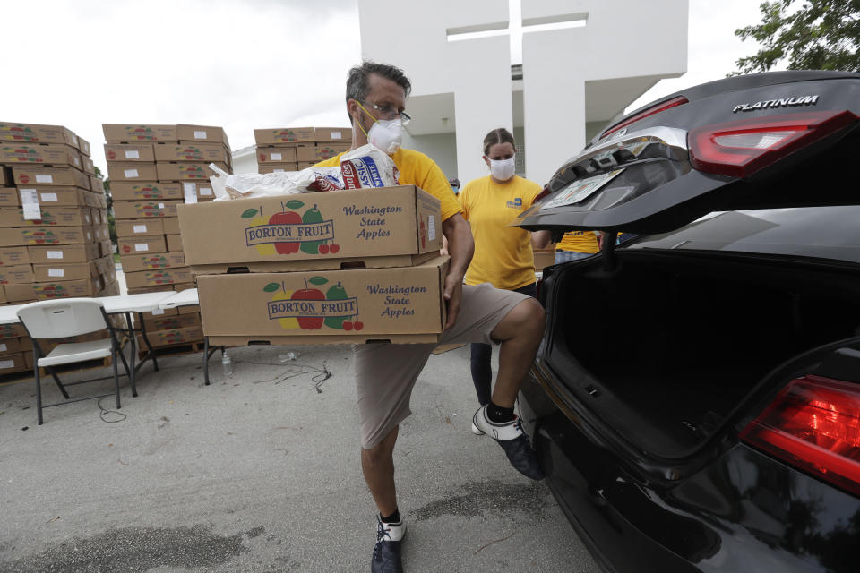 Oscar Amuz, with Volunteers in Action, loads groceries into cars during a food distribution event, Tuesday, July 21, 2020, at St. Monica's Catholic Church in Miami Gardens, Fla. (AP Photo/Wilfredo Lee)