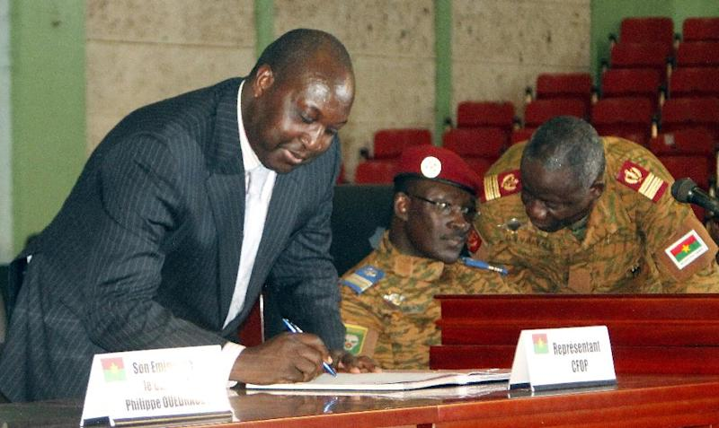 Burkina Faso's opposition leader Zephirin Diabre (L) signs a transition charter next to army-appointed leader, Lieutenant-Colonel Isaac Zida (C), and Colonel Bayala in Ouagadogou on November 16, 2014 (AFP Photo/)