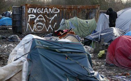 """A migrant stands next to graffiti that reads """"England pay now"""" in a muddy field at a camp of makeshift shelters for migrants and asylum-seekers from Iraq, Kurdistan, Iran and Syria, called the Grande Synthe jungle, near Dunkirk, France, January 25, 2016. REUTERS/Yves Herman"""