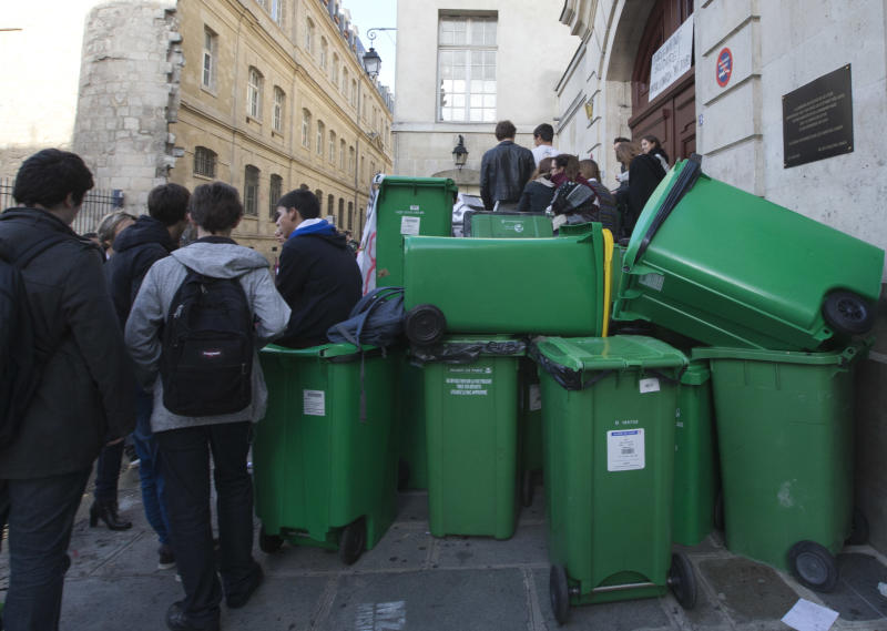 Students gather at barricades made of garbage bins protest against immigration policy, in Paris, Thursday, Oct.17, 2013. Kosovan Leonarda Dibrani was finishing up a field trip when French police showed up at the bus, detaining the 15-year-old schoolgirl in front of her classmates before authorities expelled her to Kosovo because her family's asylum application had been rejected. The incident earlier this month, but which was made public this week, has sparked outrage from immigrant groups and others who say police went too far in publicly shaming the teenager. (AP Photo/Jacques Brinon)