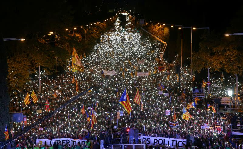 FILE PHOTO: Protesters hold the lights of their mobile phones as they wave Estelada flags during a demonstration called by pro-independence associations asking for the release of jailed Catalan activists and leaders, in Barcelona