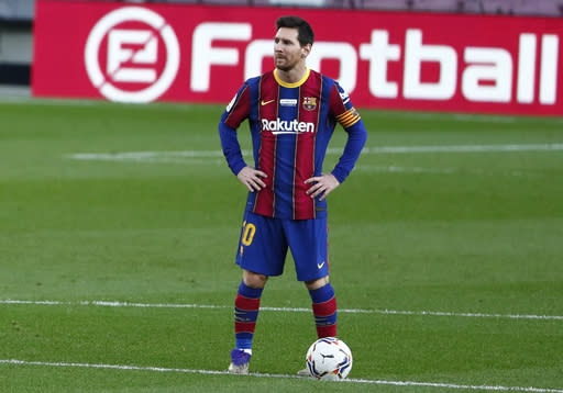 Barcelona's Lionel Messi waits in the centre circle to restart the match after Valencia scored the opening goal of the game during the Spanish La Liga soccer match between Barcelona and Valencia at the Camp Nou stadium in Barcelona, Spain, Saturday, Dec. 19, 2020. (AP Photo/Joan Monfort)