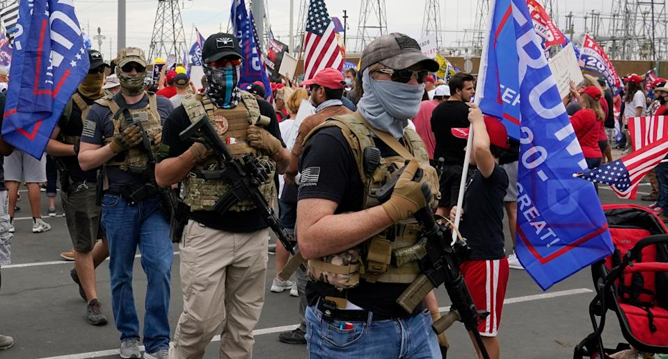 Men shown wearing face coverings and carrying guns in support of Trump.