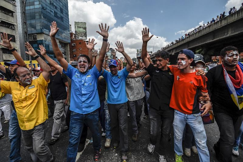 Venezuelan opposition leader and former presidential candidate Henrique Capriles (C) and opposition lawmaker Jose Manuel Olivares (L) take part in a protest in Caracas (AFP Photo/JUAN BARRETO)