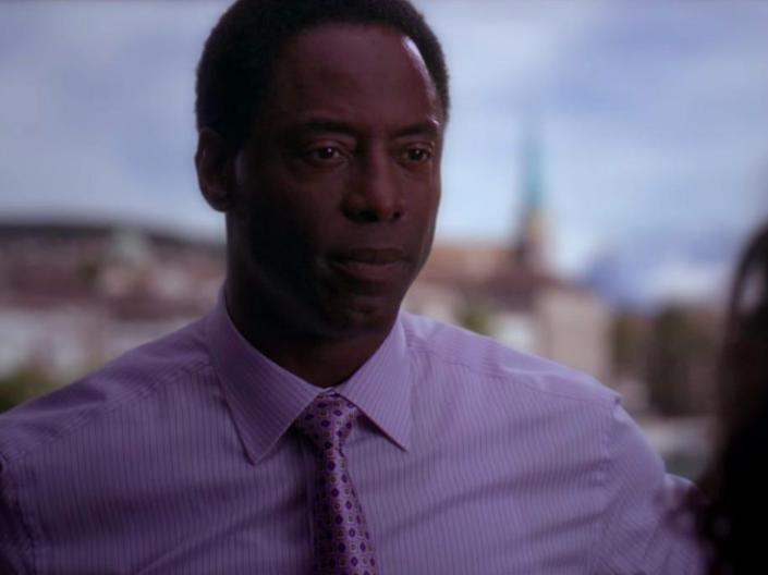 Isaiah Washinton as Burke on Greys Anatomy wearing a blue shirt with a landscape in the background