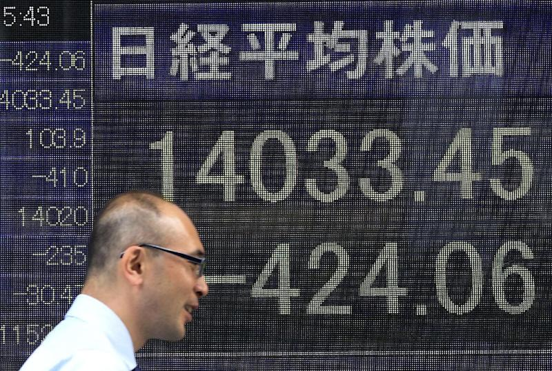 A man walks by an electronic stock board of a securities firm in Tokyo, Wednesday, May 7, 2014. A dismal day on Wall Street spilled over into Asian trading Wednesday as jitters over the valuations of technology companies contributed to a sharp drop in Japan's benchmark. The Nikkei 225 stock index fell 2.3 percent to 14,120.25. Japanese markets were closed the previous two days for public holidays. (AP Photo/Eugene Hoshiko)