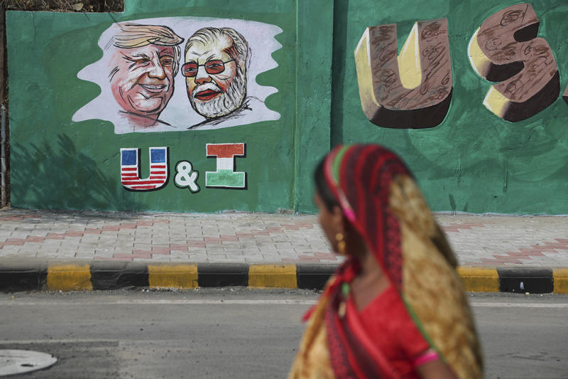 An Indian woman looks at a wall painted with portraits of President Donald Trump and Indian Prime Minister Narendra Modi ahead of Trump's visit to Ahmadabad, India.
