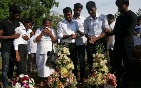 Relatives collapsed in tears at the mass burial of victims, two days after a string of suicide bomb attacks on churches and luxury hotels across the island.  - Credit:  ATHIT PERAWONGMETHA/REUTERS