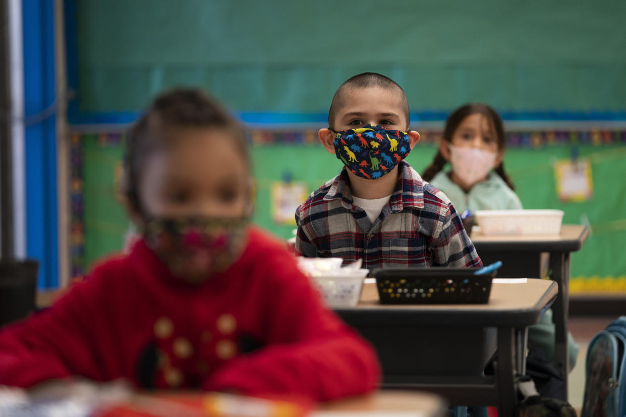 FILE — In this April 13, 2021, file photo, kindergarten students sit in their classroom on the first day of in-person learning at Maurice Sendak Elementary School in Los Angeles. California health officials announced new coronavirus rules for public schools on Monday, July 12, 2021. The new rules eliminate physical distancing while making sure no one will miss class time even if they are exposed to someone with the virus. But the state would continue to require all students and staff to wear masks indoors. (AP Photo/Jae C. Hong, File)