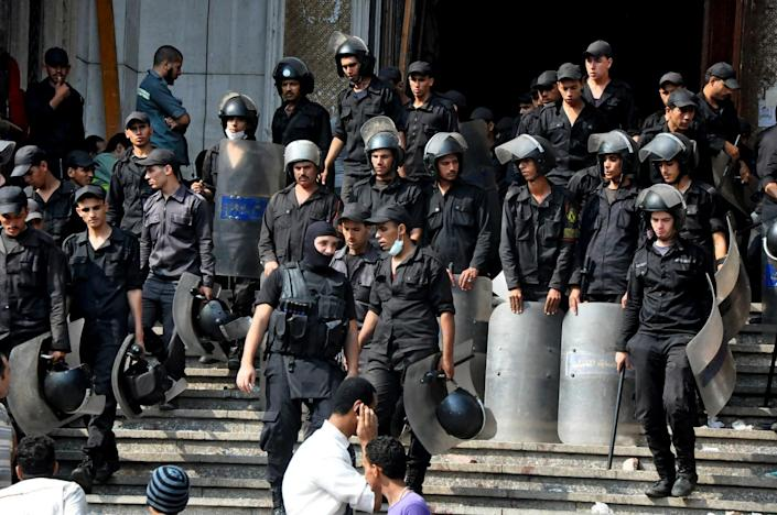 Egyptians security forces provide a cordon around the al-Fatah mosque, after hundreds of Muslim Brotherhood supporters barricaded themselves inside the mosque overnight, following a day of fierce street battles that left scores of people dead, near Ramses Square in downtown Cairo, Egypt, Saturday, Aug. 17, 2013. Authorities say police in Cairo are negotiating with people barricaded in a mosque and promising them safe passage if they leave. Muslim Brotherhood supporters of Egypt's ousted Islamist president are vowing to defy a state of emergency with new protests today, adding to the tension. (AP Photo/Hussein Tallal)