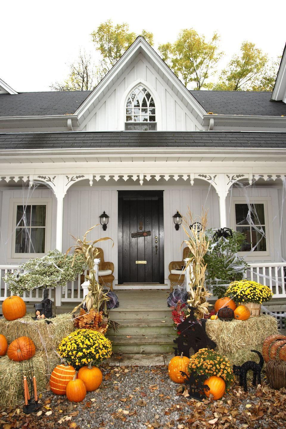 <p>Create a classic country Halloween vignette on your front porch by arranging hay bales, mums, pumpkins, and dried corn stalks around your steps. Fake spiderwebs add a not-too-scary touch. </p>