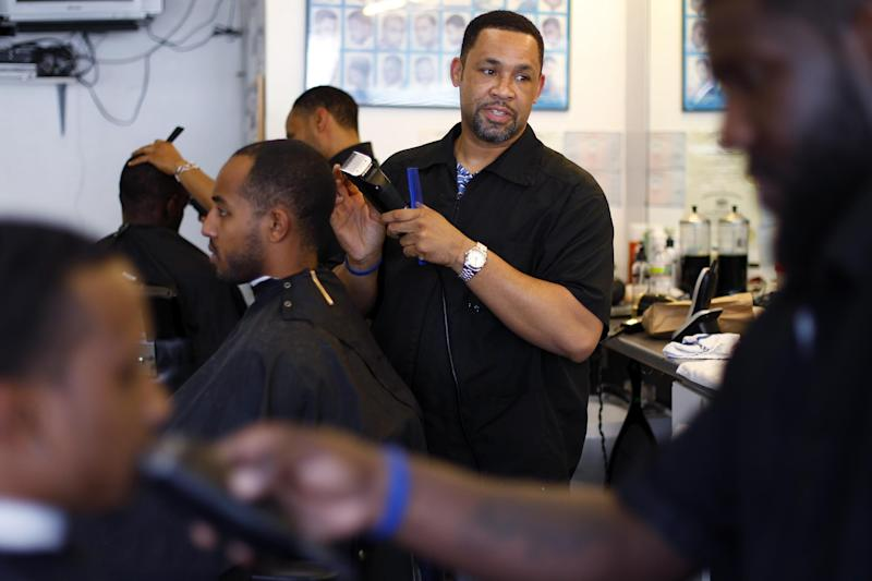 """Dorsey Jackson cuts hair at his establishment Jackson's Barbershop, Friday, May 11, 2012, in Ardmore, Pa. Like many black Americans, Dorsey Jackson does not believe in gay marriage, but he wasn't disillusioned when Barack Obama became the first president to support it. The windows of his suburban Philadelphia barbershop still display an """"Obama 2012"""" placard and another that reads """"We've Got His Back.""""(AP Photo/Matt Rourke)"""