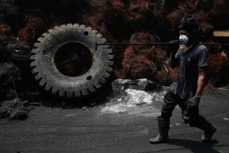 A worker passes steel wires and a tyre at a tyre pyrolysis plant in Kulai