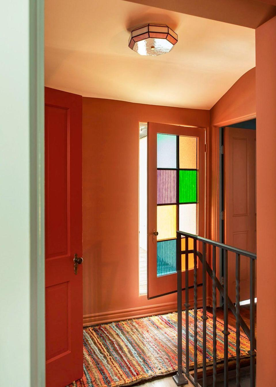 """<p>This hallway by <a href=""""https://www.reathdesign.com/"""" rel=""""nofollow noopener"""" target=""""_blank"""" data-ylk=""""slk:Reath Design"""" class=""""link rapid-noclick-resp"""">Reath Design</a> proves that rainbow decorating can be energizing without being overly stimulating. With multi-colored panes and a striped carpet, this is another example of a transitional space being much more than just a place to get you room to room. </p>"""
