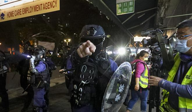 A riot police officer points at a photographer during a rally commemorating eight months since the violent mob attack in Yuen Long. Photo: Dickson Lee