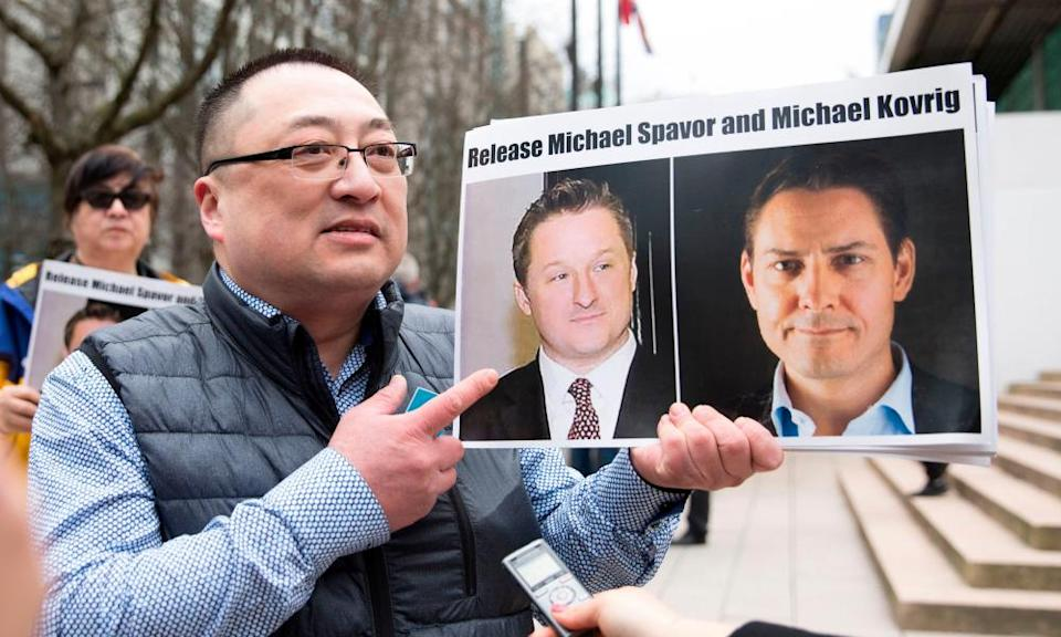 A protester holds photos of Canadians Michael Spavor and Michael Kovrig, who are being detained by China, outside British Columbia supreme court, in Vancouver.