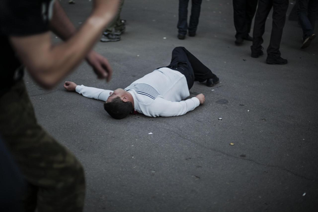 The body of a pro-Russia man lies on the ground in Krasnoarmeisk, Ukraine, Sunday, May 11, 2014. Although the voting in the Donetsk and Luhansk regions appeared mostly peaceful, Ukrainian national guardsmen opened fire on a crowd outside a town hall in Krasnoarmeisk, and an official with the region's insurgents said there were fatalities. (AP Photo/Manu Brabo)
