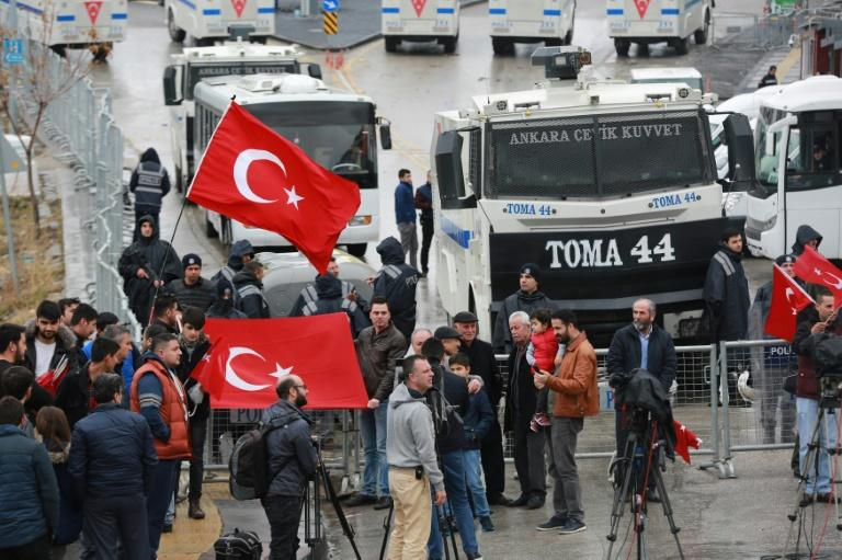 Demonstrators wave the Turkish national flag by a blockade of anti-riot police vehicles and a sealed off area surrounding the Dutch embassy in Ankara on March 12, 2017