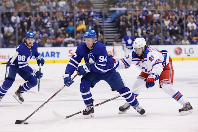New York Rangers center Mika Zibanejad (93) tries to chase down the puck from Toronto Maple Leafs defenseman Tyson Barrie (94) during second-period NHL hockey game action in Toronto, Saturday, Dec. 28, 2019. (Cole Burston/The Canadian Press via AP)