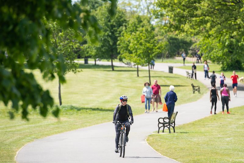 People walk and exercise in the sun in Brockwell Park, south London, after the announcement of plans to bring the country out of lockdown. (Photo by Dominic Lipinski/PA Images via Getty Images)