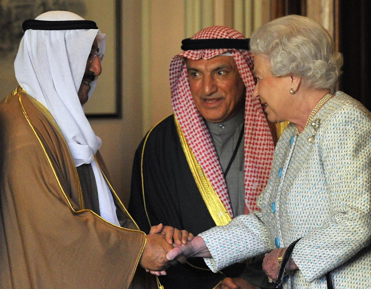 Britain's Queen Elizabeth II (R) shakes hands with the Kuwait's Emir Sheikh Sabah al-Ahmad al-Sabah (L) at Windsor Castle in Windsor on the last day of his state visit to the UK.