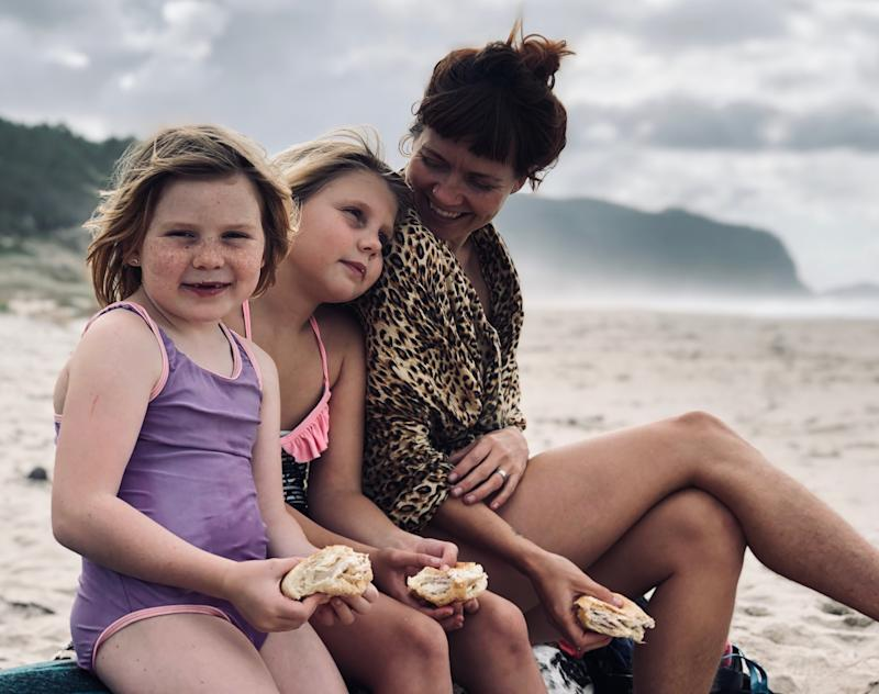 Mum sitting eating a sandwich at the beach with her two daughters.
