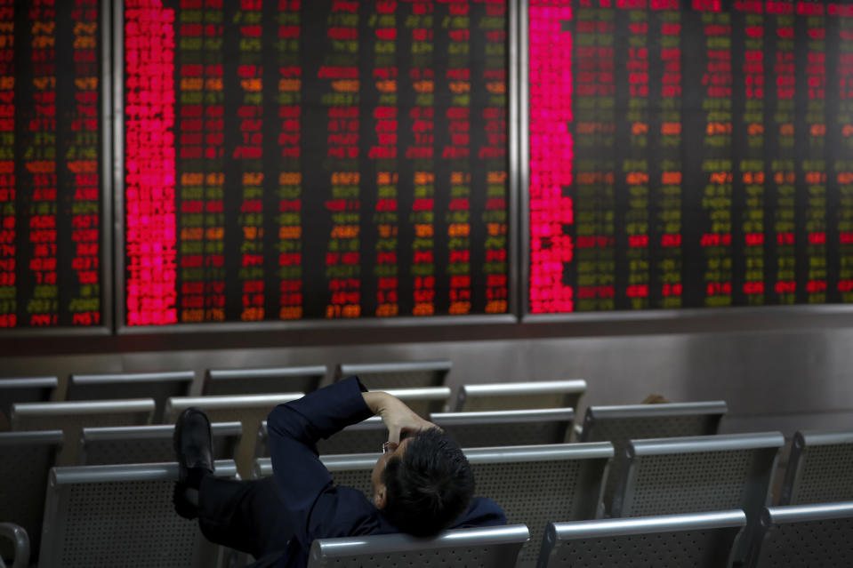 An investor presses his forehead in front of an electronic board displaying stock prices at a brokerage house in Beijing, Wednesday, Oct. 16, 2019. Asian shares were higher Wednesday after a gain on Wall Street boosted by healthy earnings reports from U.S. companies. (AP Photo/Andy Wong)
