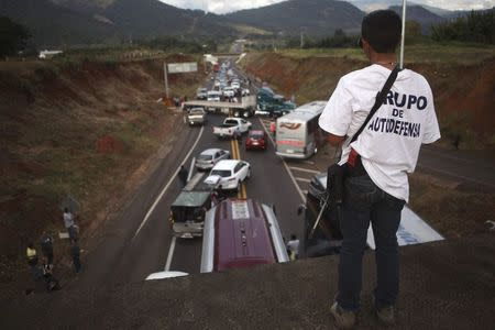 A vigilante stands guard on a bridge during a blockade on a highway near the town of Uruapan in Michoacan state, December 14, 2014. REUTERS/Alan Ortega/Files