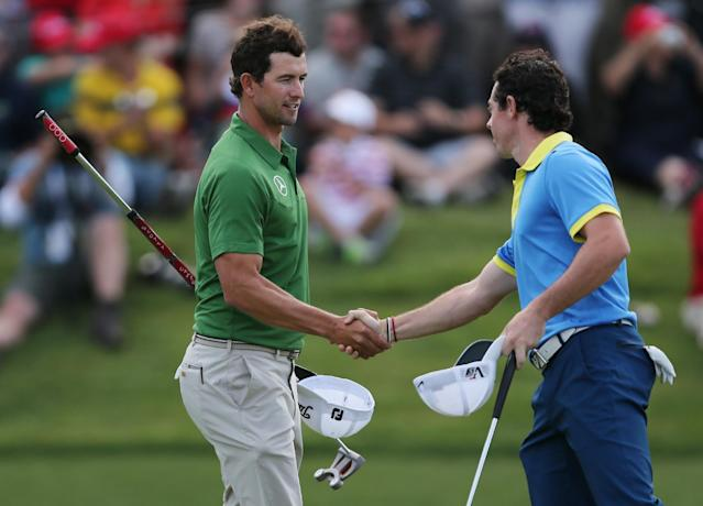 Rory McIlroy, right, of Northern Ireland shakes hands with Australia's Adam Scott following their third round at the Australian Open Golf tournament in Sydney, Australia, Saturday, Nov. 30, 2013.(AP Photo/Rob Griffith)