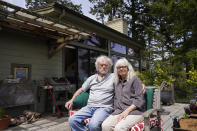 Gordon Bennett and his wife Kate Carolan sit outside their home, Friday, April 30, 2021, in Inverness, Calif. The couple, who were victims of Bernard Madoff and forced to sell their home, now rent it back from someone they know who purchased it. More than 12 years after Madoff confessed to running the biggest financial fraud in Wall Street history, a team of lawyers is still at work on a sprawling effort to recover money for the thousands of victims of his scam. (AP Photo/Eric Risberg)