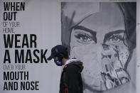 """FILE - In this Saturday, Nov. 21, 2020, file photo, a pedestrian walks past a mural reading: """"When out of your home, Wear a mask over your mouth and nose,"""" during the coronavirus outbreak in San Francisco. San Francisco is joining a statewide curfew and Silicon Valley is banning all high school, collegiate and professional sports and imposing a quarantine for those traveling into the region from more than 150 miles away. Santa Clara County has the highest case rate in the Bay Area, leading to the stricter rules, said Santa Clara County Health Officer Dr. Sara Cody. (AP Photo/Jeff Chiu, File)"""