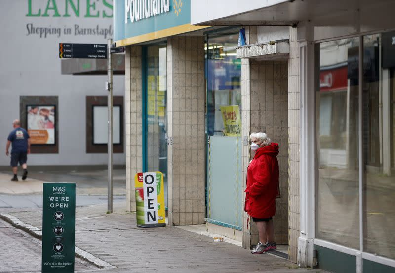 An elderly woman wearing a protective face mask looks on at High Street in Barnstaple