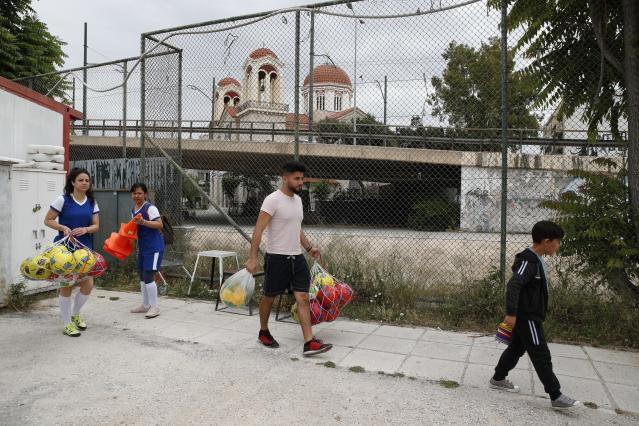 In this Wednesday, May 22, 2019 photo, members of Hestia FC Women's Refugee Soccer team prepare for a training session in Athens. Many of the players at Hestia FC weren't allowed to play or even watch soccer matches in their home countries. Hestia FC was set up by the Olympic Truce Centre, a non-government organization created in 2000 by the International Olympic Committee and Greek Foreign Ministry. (AP Photo/Thanassis Stavrakis)