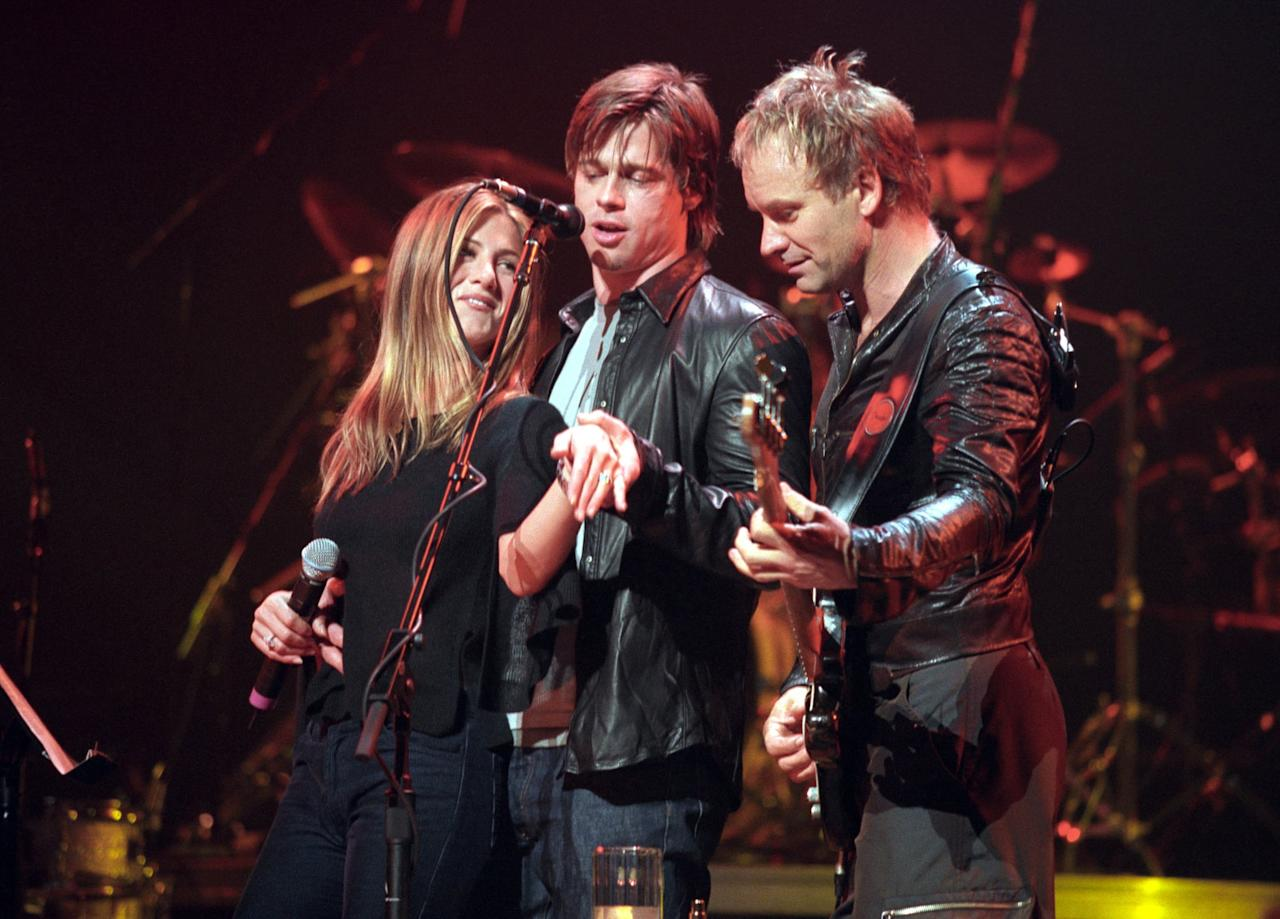 """<p>Only a few months after making their red carpet debut, Brad and Jen attended a Sting concert at the Beacon Theater in NYC on Nov. 16, 1999, where they went up on stage so Jen could show the rock star her new rock - <a href=""""http://people.com/archive/cover-story-isnt-it-romantic-vol-54-no-7/"""" target=""""_blank"""" class=""""ga-track"""" data-ga-category=""""Related"""" data-ga-label=""""http://people.com/archive/cover-story-isnt-it-romantic-vol-54-no-7/"""" data-ga-action=""""In-Line Links"""">a diamond-and-platinum engagement ring</a> from Italian jewelry designer Silvia Damiani. Jen reportedly joined Sting at the microphone to sing """"Fill 'Er Up,"""" and during the song, Brad put his arm around Jen and showed off her bedazzled hand to the audience. Though <a href=""""http://news.bbc.co.uk/2/hi/entertainment/534772.stm"""" target=""""_blank"""" class=""""ga-track"""" data-ga-category=""""Related"""" data-ga-label=""""http://news.bbc.co.uk/2/hi/entertainment/534772.stm"""" data-ga-action=""""In-Line Links"""">Jen's spokesperson claimed it was not an engagement ring</a>, and Brad's spokesperson said it was a joke, since """"Fill 'Er Up"""" is about getting married, it soon became clear that the engagement was legit.</p>"""