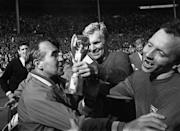 England Manager Alf Ramsey (left) celebrates his team's 4-2 victory in extra time over West Germany in the World Cup Final at Wembley Stadium. With him is captain Bobby Moore (1941 - 1993), holding the Jules Rimet Trophy, and team mate Nobby Stiles, 30th July 1966. (Photo by Hulton Archive/Getty Images)