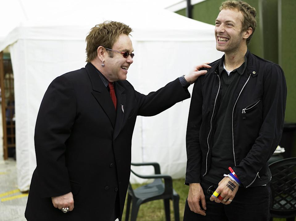 """LONDON - JULY 2:  (MINIMUM FEE OF GBP250, OR LOCAL EQUIVALENT, PER IMAGE.ONLY FOR USE IN CONTEXT OF LIVE 8. NO USE THAT IS DEROGATORY OR DAMAGING TO THE BAND AID TRUST, LIVE 8 OR MAKE POVERTY HISTORY. NO SALES FOR ON-LINE USE) Musicians Sir Elton John and Chris Martin of Coldplay talk backstage at """"Live 8 London"""" in Hyde Park on July 2, 2005 in London, England. The free concert is one of ten simultaneous international gigs including Philadelphia, Berlin, Rome, Paris, Barrie, Tokyo, Cornwall, Moscow and Johannesburg. The concerts precede the G8 summit (July 6-8) to raising awareness for MAKEpovertyHISTORY.  (Photo by Kevin Westenberg/Live 8 via Getty Images)"""