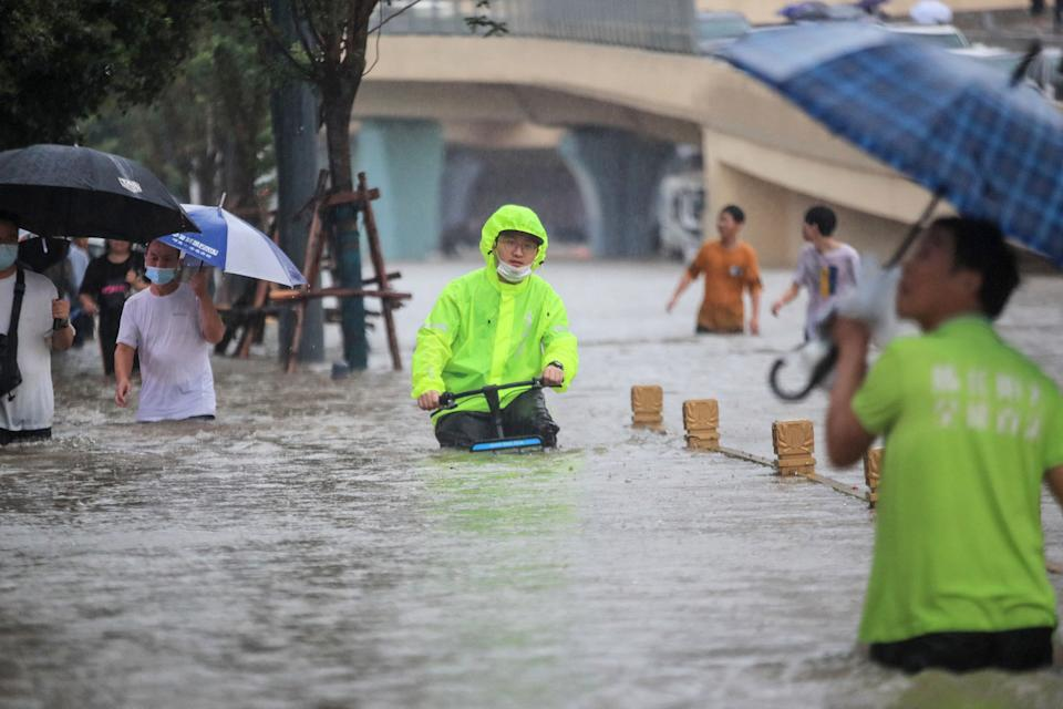 This photo taken on July 20, 2021 shows a man riding a bicycle through flood waters along a street following heavy rains in Zhengzhou in China's central Henan province. - - China OUT (Photo by STR / AFP) / China OUT (Photo by STR/AFP via Getty Images)