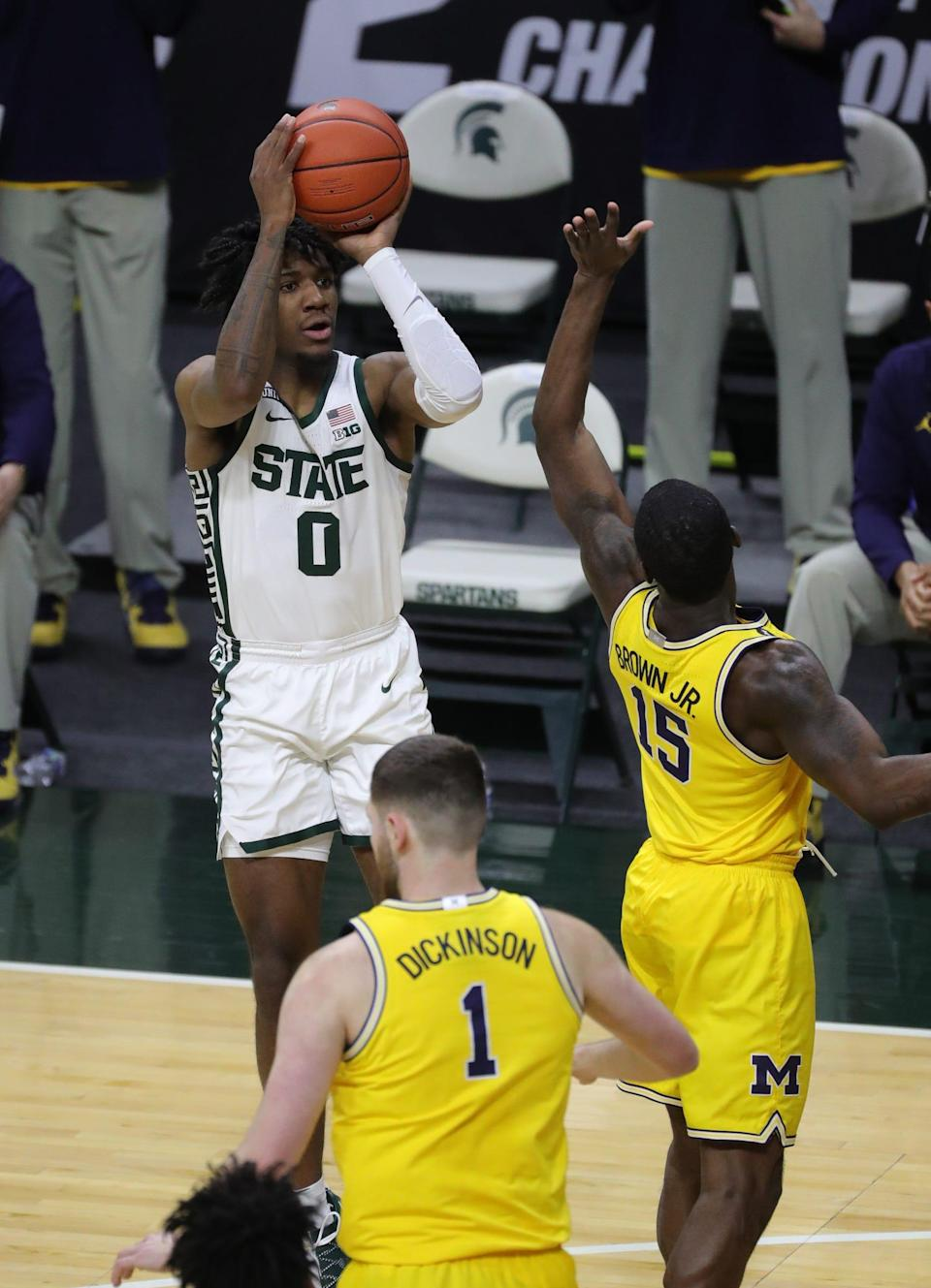 Michigan State Spartans forward Aaron Henry scores against Michigan Wolverines guard Chaundee Brown on Sunday, March 7, 2021, at the Breslin Center in East Lansing.