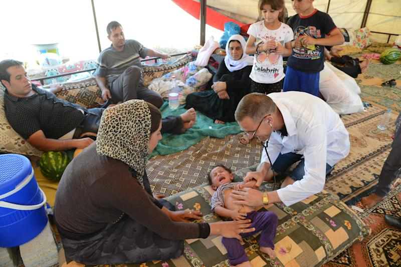 A doctor checks an Iraqi baby from the Yazidi community in a refugee camp near the Turkey-Iraq border at Silopi in Sirnak on August 14, 2014 (AFP Photo/Ilyas Akengin)