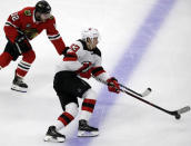 New Jersey Devils left wing Jesper Bratt, right, controls the puck against Chicago Blackhawks left wing Alex DeBrincat during the first period of an NHL hockey game Thursday, Feb. 14, 2019, in Chicago. (AP Photo/Nam Y. Huh)