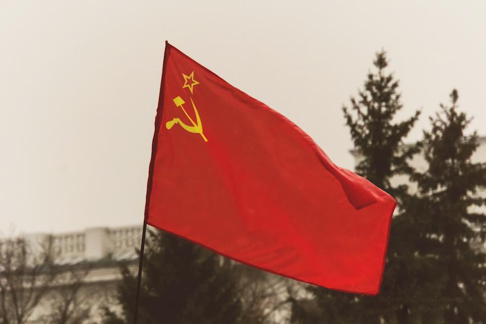 Old shabby red flag of the USSR on the flagstaff. The flag depicts a star and a sickle and a hammer. great October revolution