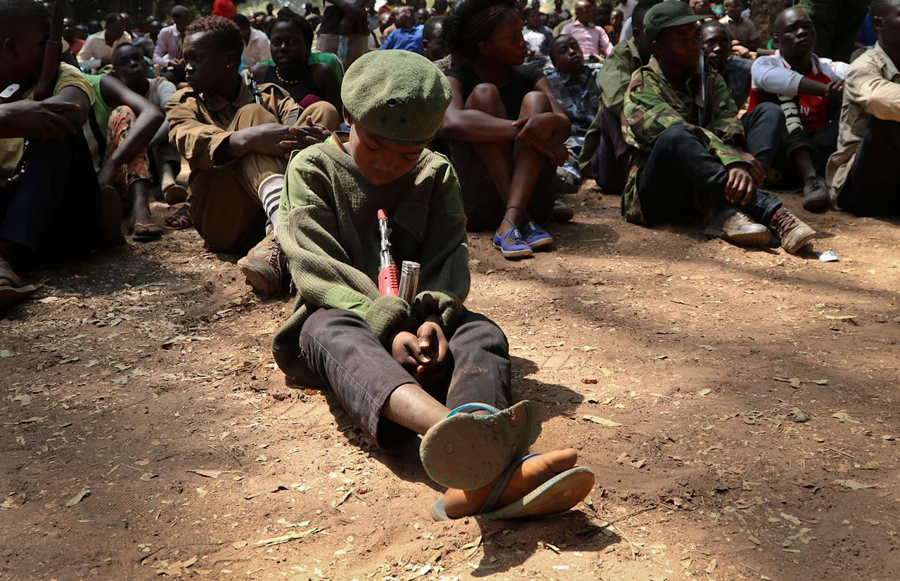 "<p>A young child soldier sits on the ground at a release ceremony, where he and others laid down their weapons and traded in their uniforms to return to ""normal life"", in Yambio, South Sudan Wednesday, Feb. 7, 2018. (Photo: Sam Mednick/AP) </p>"
