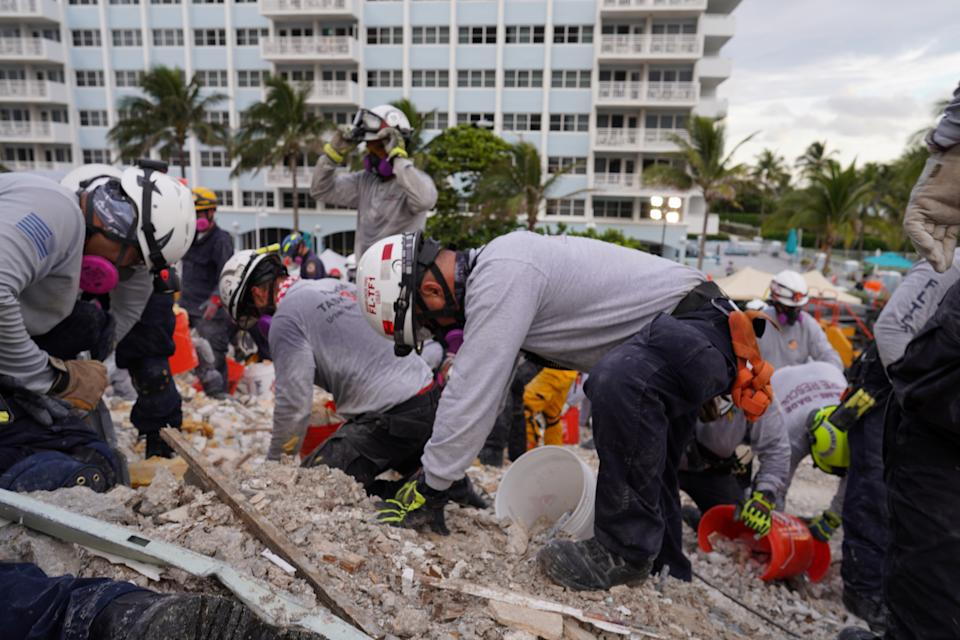 Rescue workers dig through the rubble at the partially collapsed building in Surfside, Fla., Tuesday. (MDFR/Handout via Reuters)