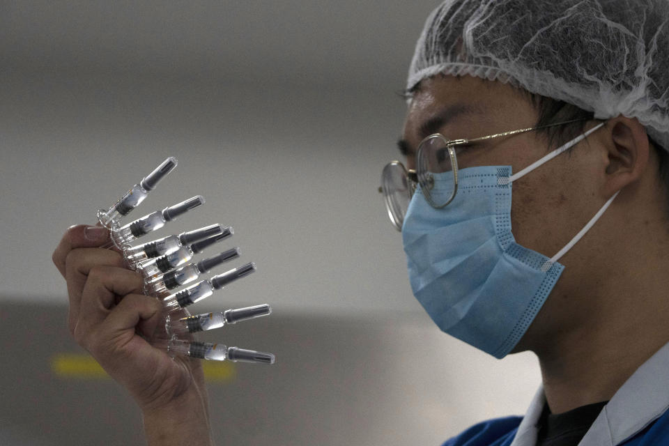 An employee manually inspects syringes of the SARS CoV-2 Vaccine for COVID-19 produced by SinoVac at its factory in Beijing on Thursday, Sept. 24, 2020. A Chinese health official said Friday, Sept. 25,2020, that the country's annual production capacity for coronavirus vaccines will top 1 billion doses next year, following an aggressive government support program for construction of new factories. (AP Photo/Ng Han Guan)