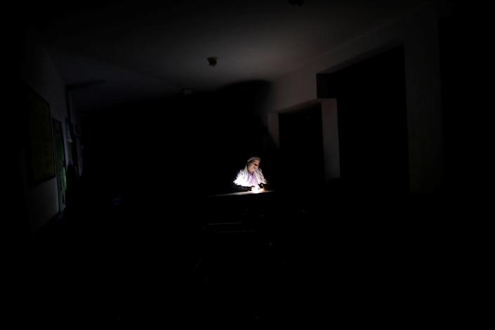 A nurse waits for the electricity to return at a dialysis center during a blackout in Maracaibo, Venezuela. (Photo: Ueslei Marcelino/Reuters)